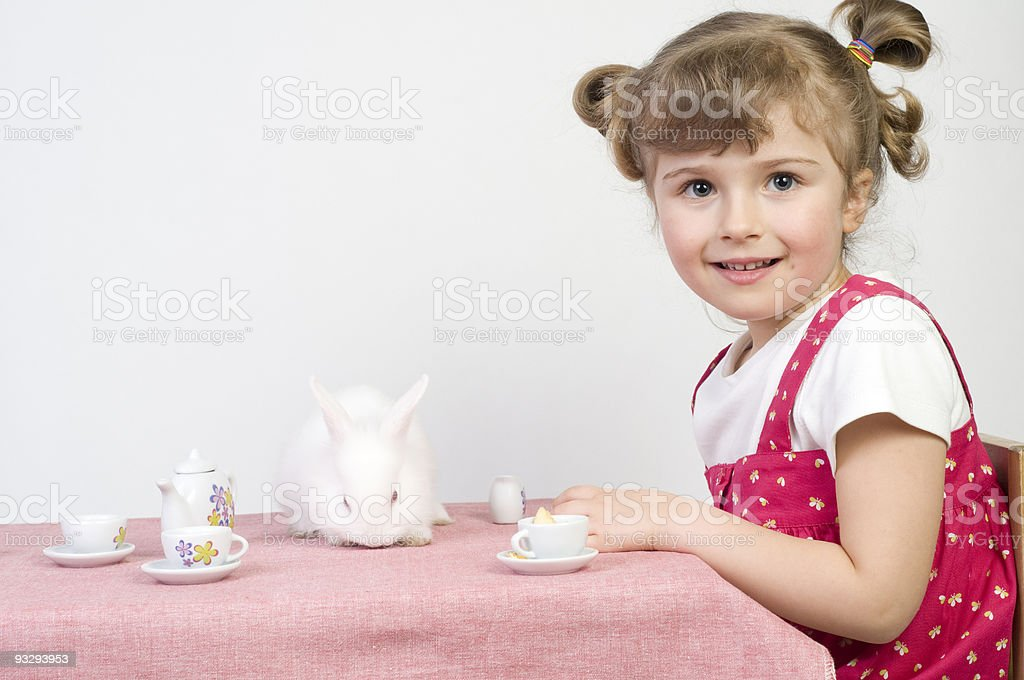 Little girl playing with baby rabbit royalty-free stock photo