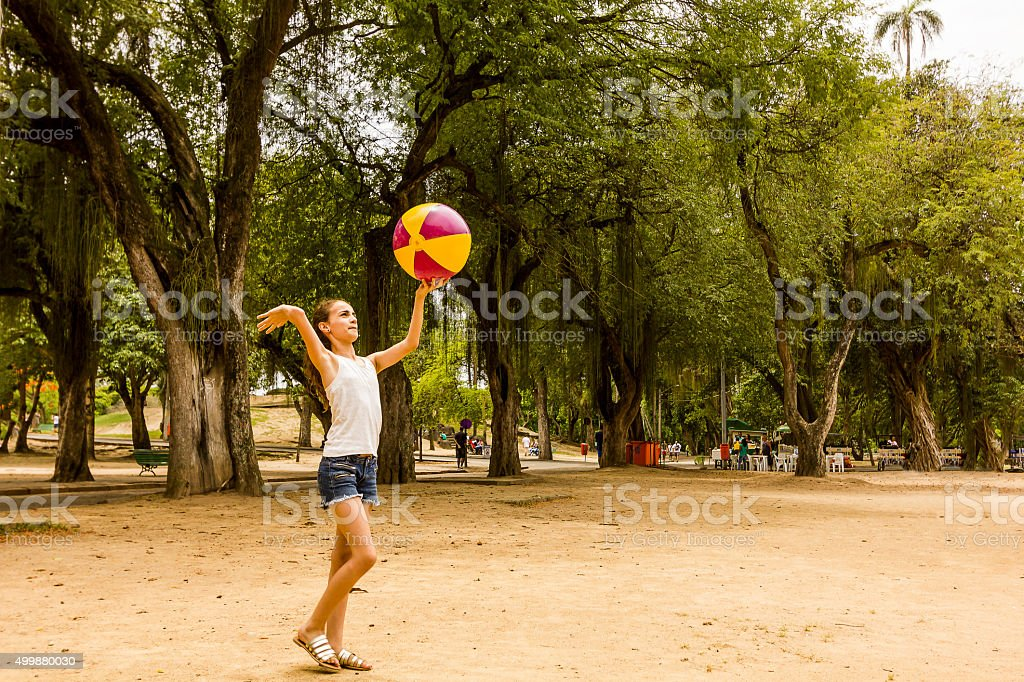 Little Girl Playing with Ball on a Park stock photo