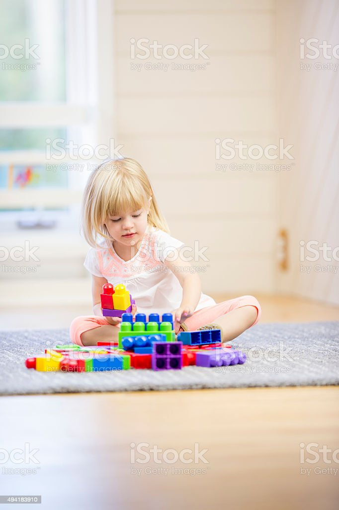 Little Girl Playing with Blocks at Home stock photo