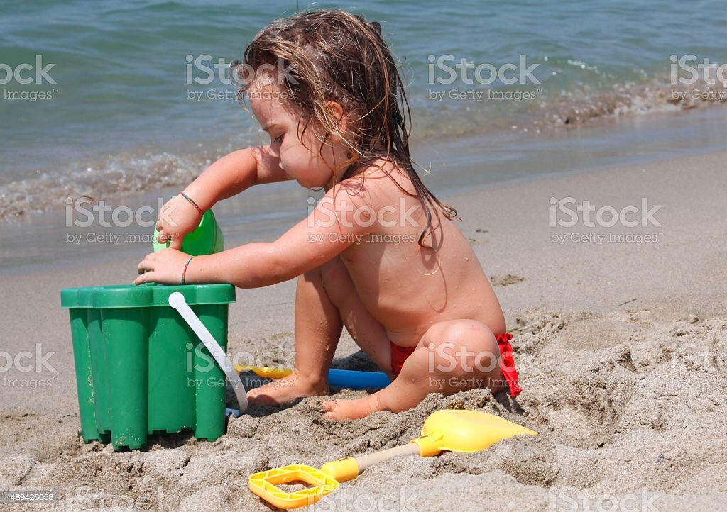 little girl playing with bucket and spade on the beach stock photo