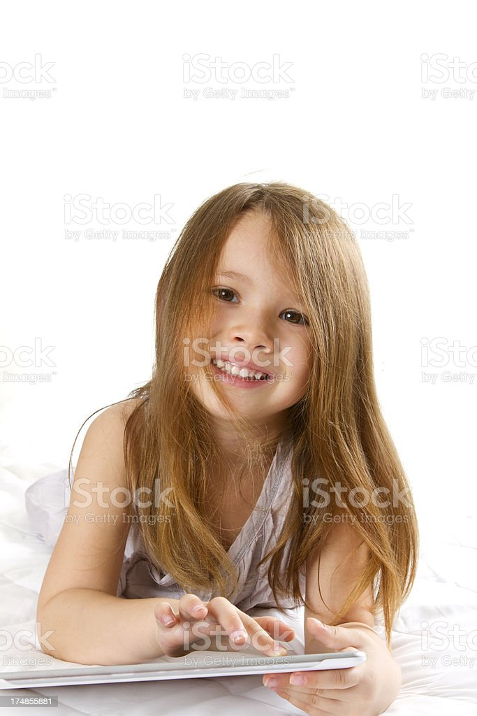 Little girl playing with digital tablet isolated on white stock photo