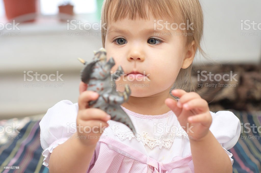 Little girl playing with dinosaur toy stock photo