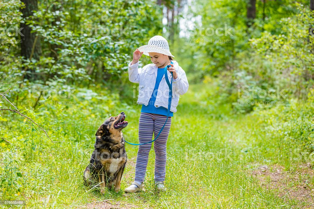 Little girl playing with dog in the forest stock photo