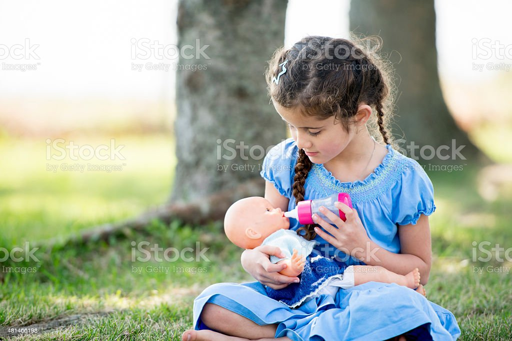 Little Girl Playing with Doll at Park stock photo