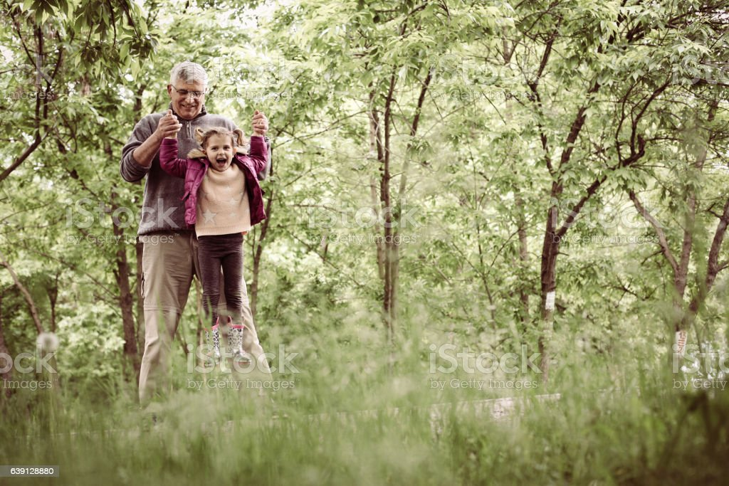 Little girl playing with grandfather in the park. stock photo