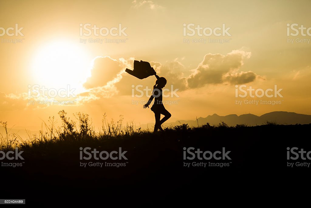 Little Girl Playing with her Coat Silhouetted by Setting Sun stock photo