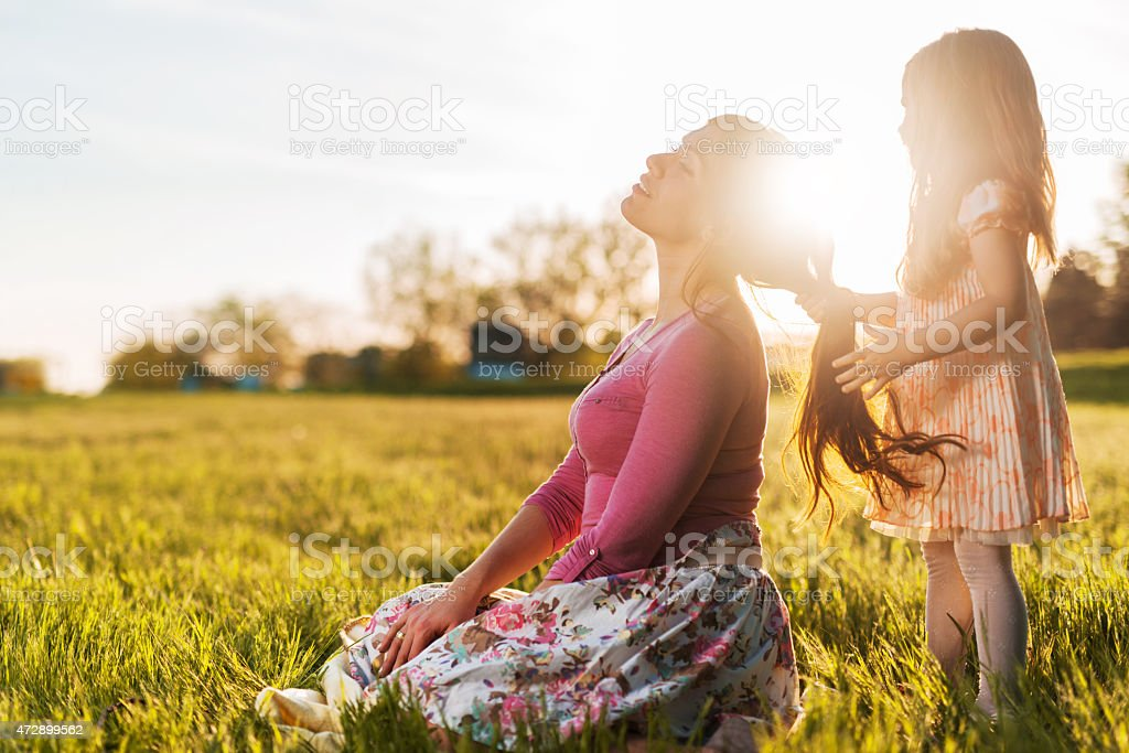 Little girl playing with her mother's hair during spring day. stock photo