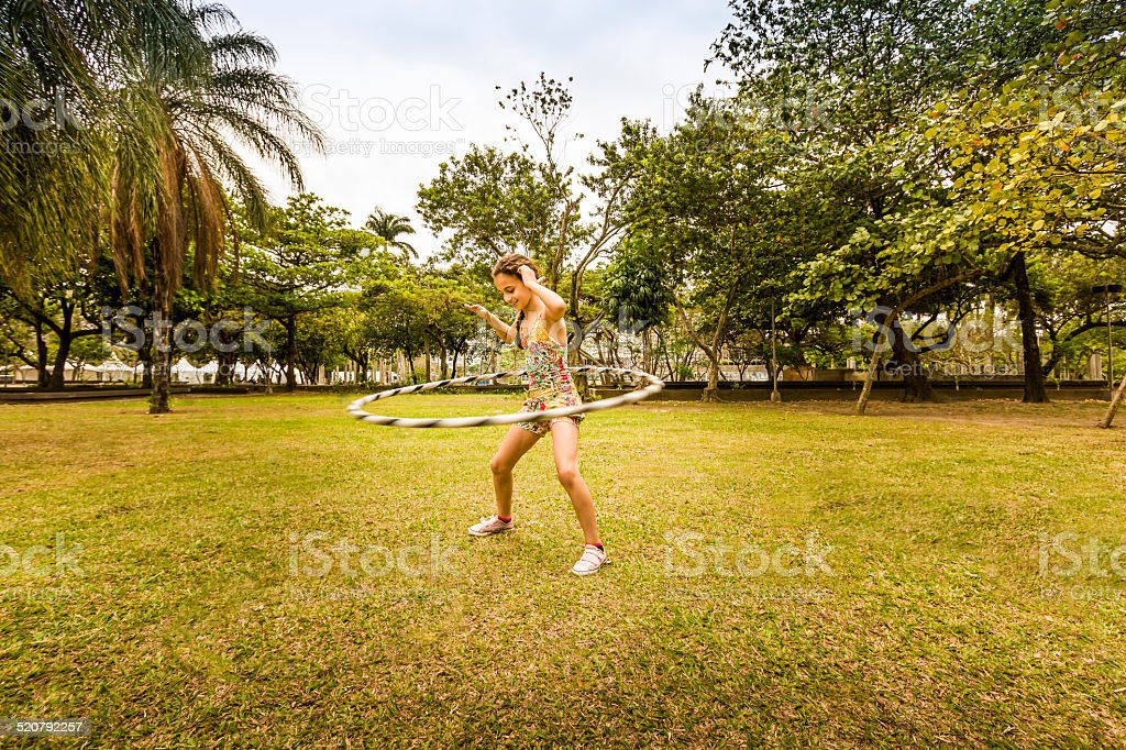 Little Girl Playing with Hula Hoop in Park stock photo