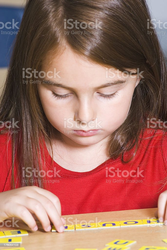 Little girl playing with letters in the classroom - IV royalty-free stock photo