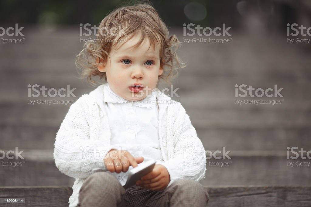 Little girl playing with mobile phone stock photo