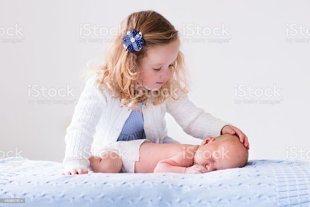 Little girl playing with newborn baby brother stock photo