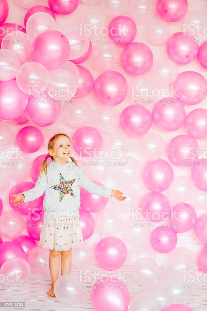 little girl playing with pink balloons stock photo