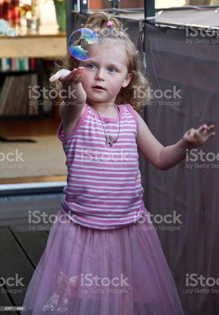 Little girl playing with soap bubble stock photo