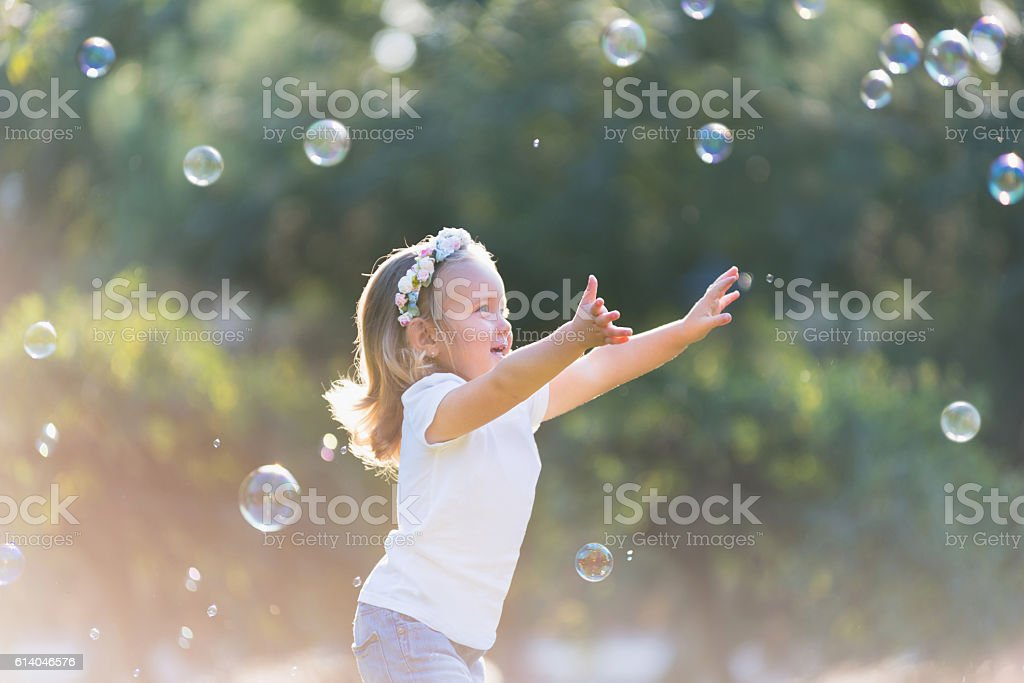 little girl playing with soap bubbles stock photo