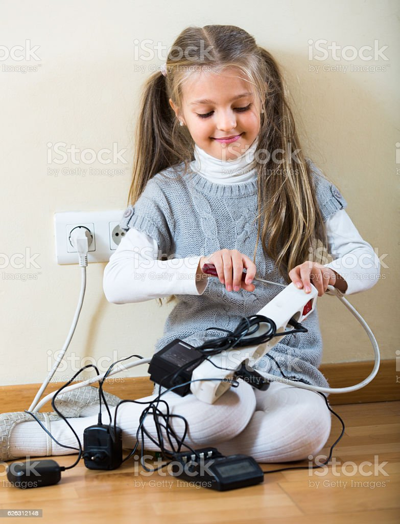 Little girl playing with sockets at home stock photo