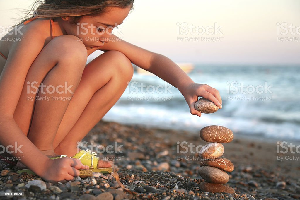little girl playing with stones on beach stock photo