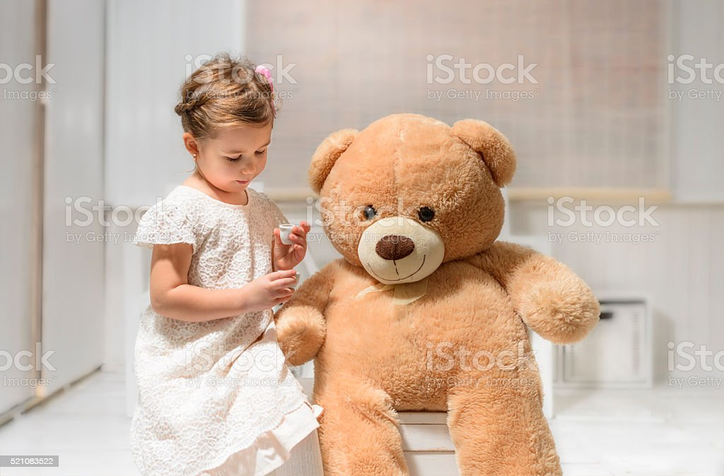 Little girl playing with teddy bear stock photo