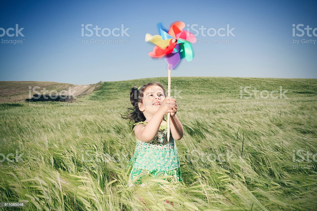 Little girl playing with toy windmill stock photo