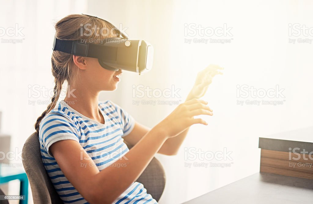 Little girl playing with virtual reality headset stock photo