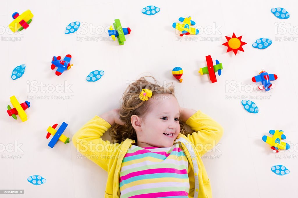 Little girl playing with wooden airplane stock photo