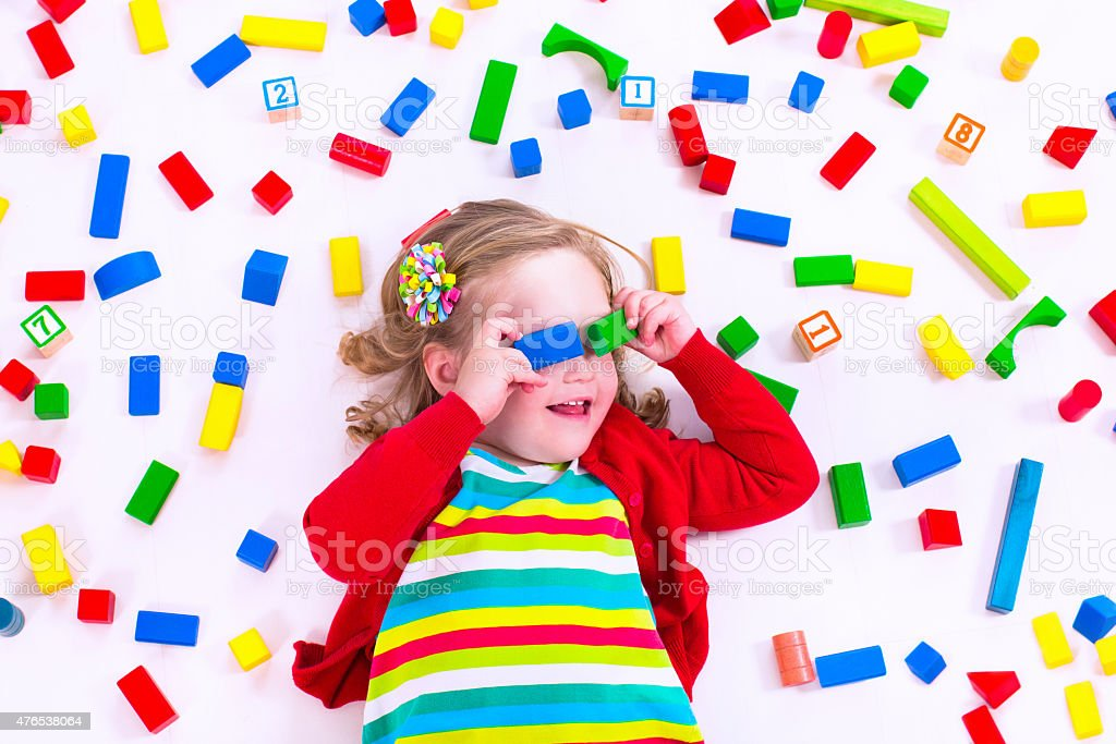 Little girl playing with wooden blocks stock photo