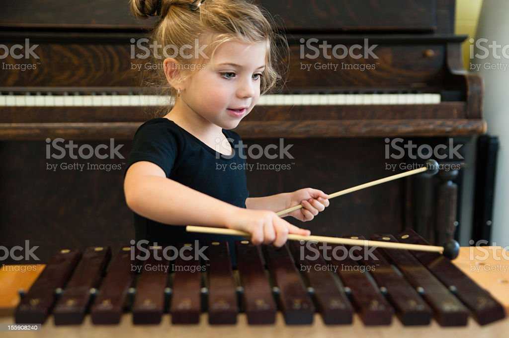 Little girl playing xylophone with piano in background, horizontal. stock photo
