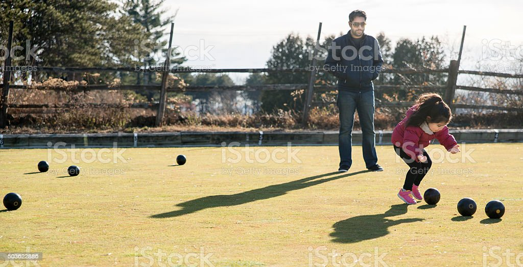 Little girl plays bowls at the lawn stock photo