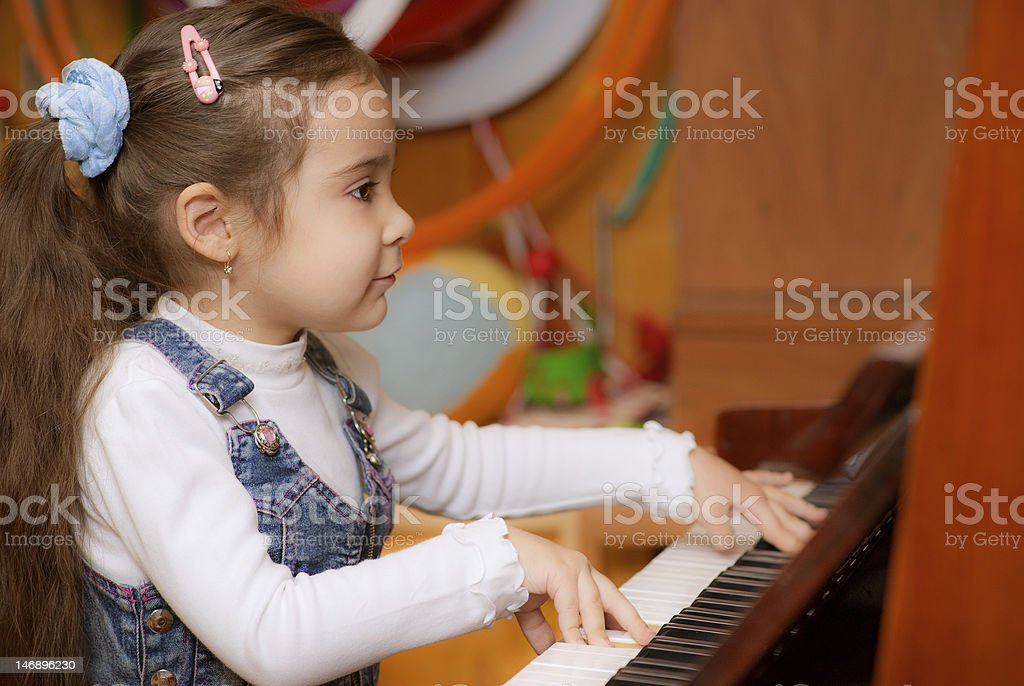 Little girl plays piano stock photo