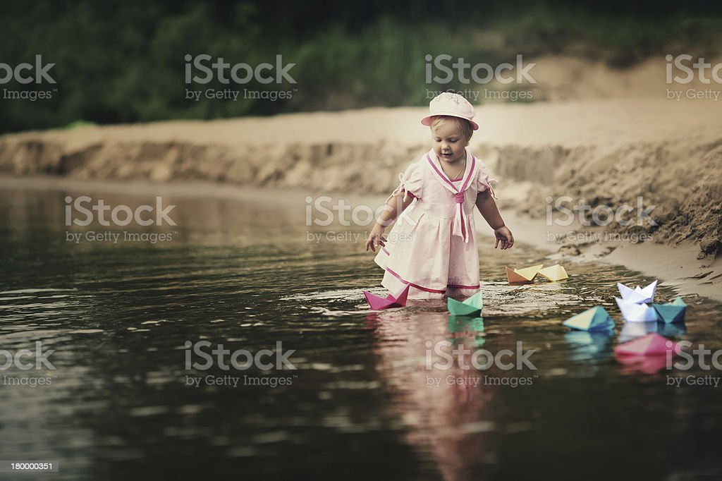 little girl plays with paper boats royalty-free stock photo