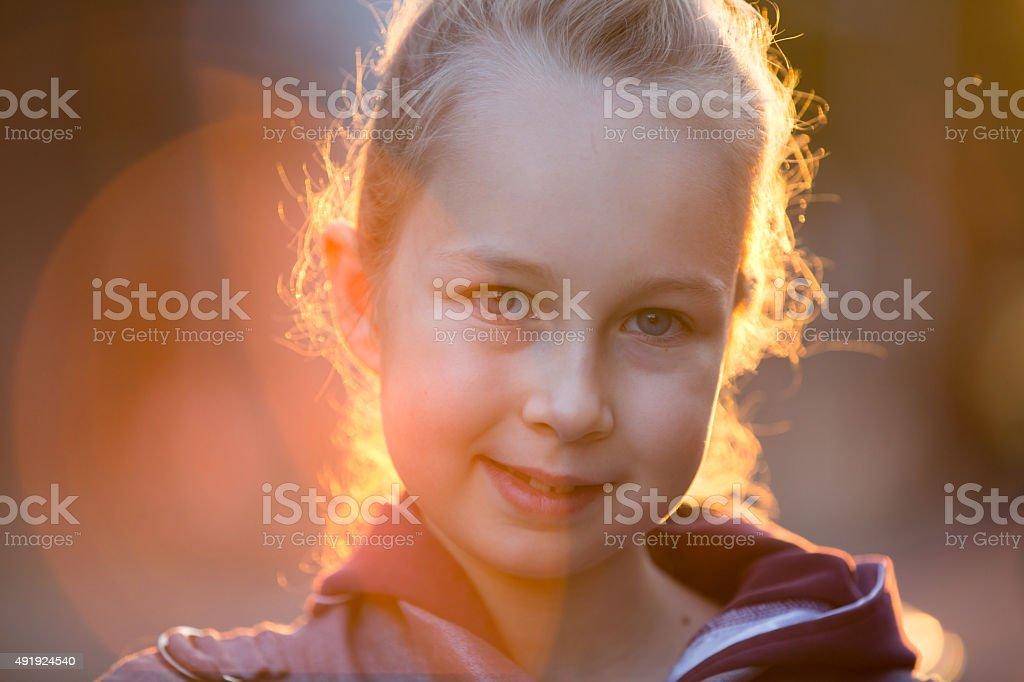 Little girl portrait against of sunset stock photo