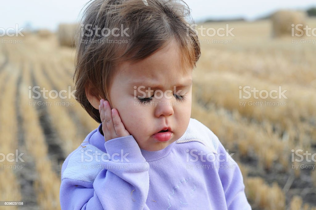 Little girl portrait complaining an ache stock photo