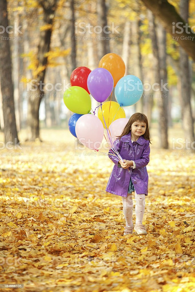 Little girl posing with balloons in nature royalty-free stock photo