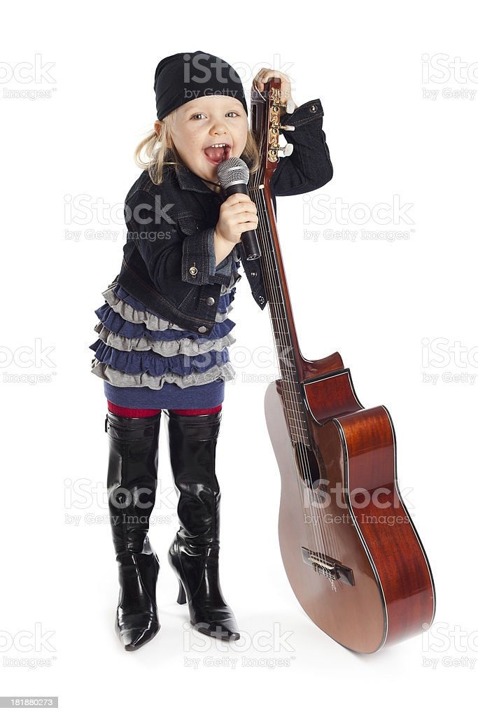 Little girl posing with guitar and microphone stock photo