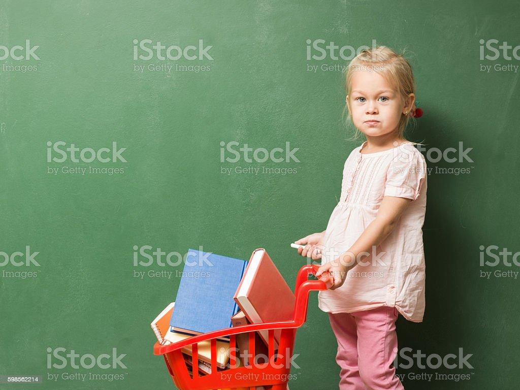 Little Girl Posing With Shopping Cart Full Of Books stock photo