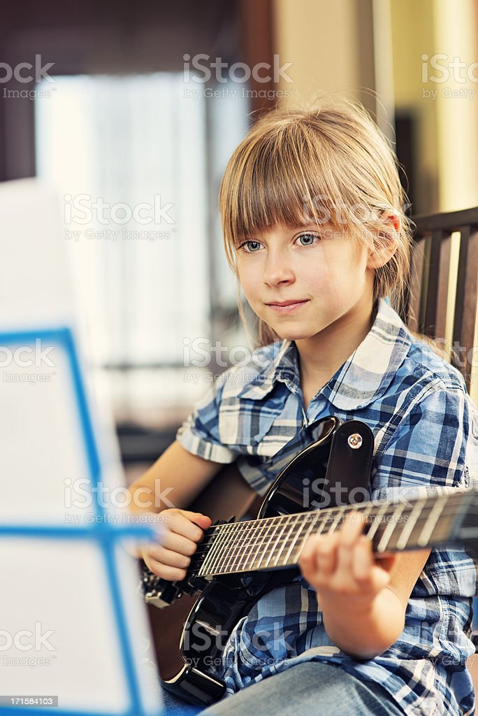 Little girl practicing her guitar royalty-free stock photo
