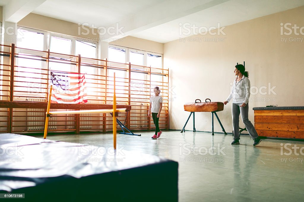 Little Girl Practicing High Jump With Her Instructor. stock photo