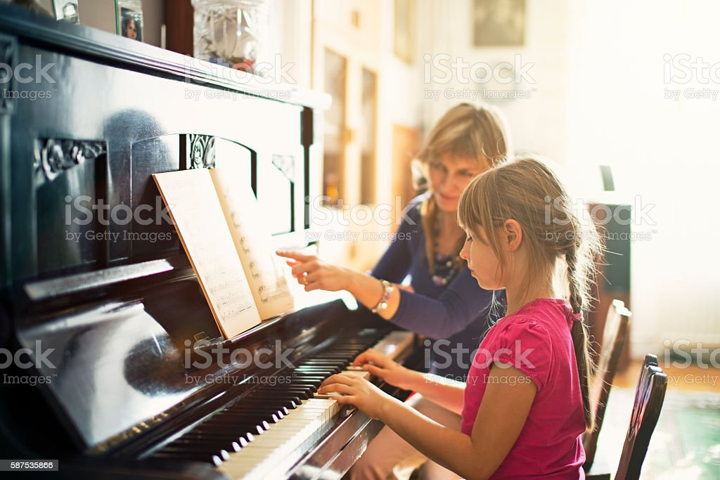 Little girl practicing piano stock photo