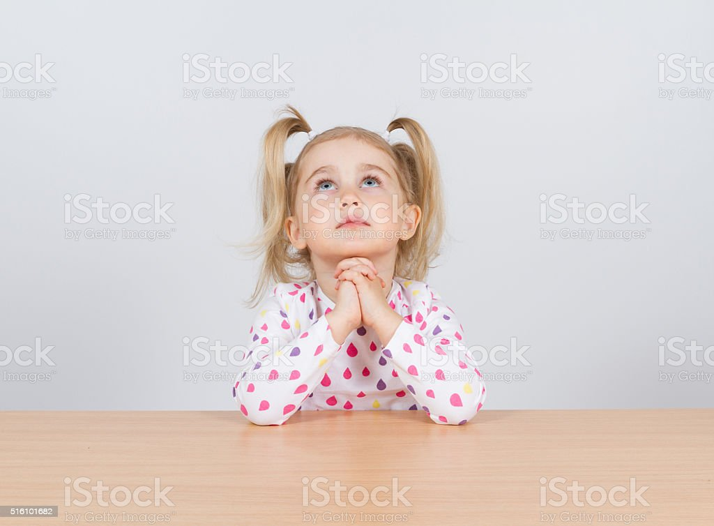 Little girl praying and looking up. stock photo