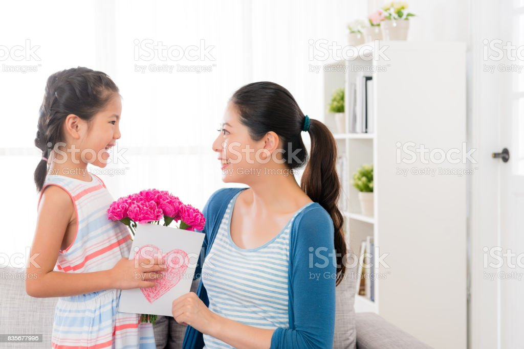 little girl prepare a pink carnation bouquet stock photo