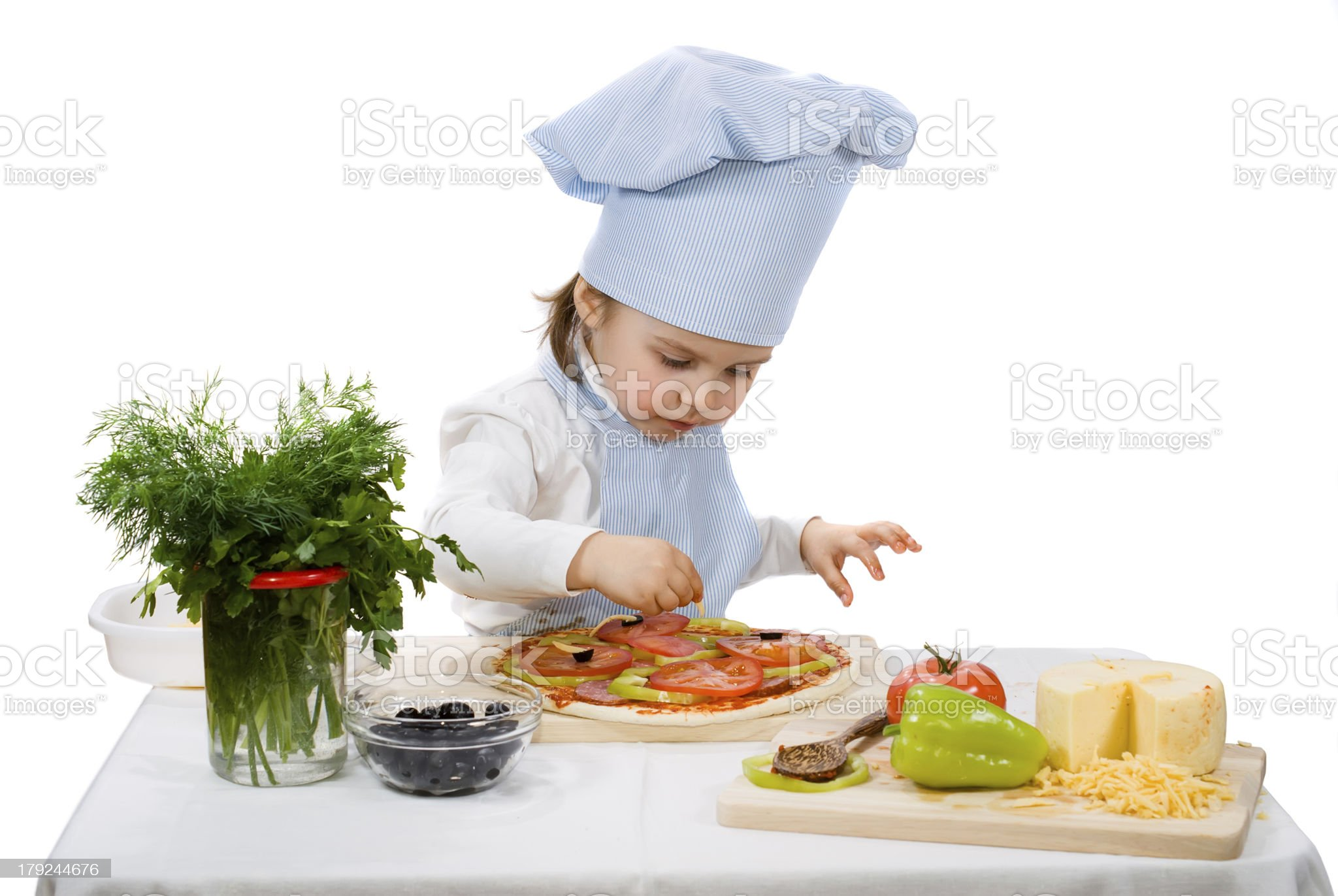little girl preparing a pizza with cheese and vegetables royalty-free stock photo
