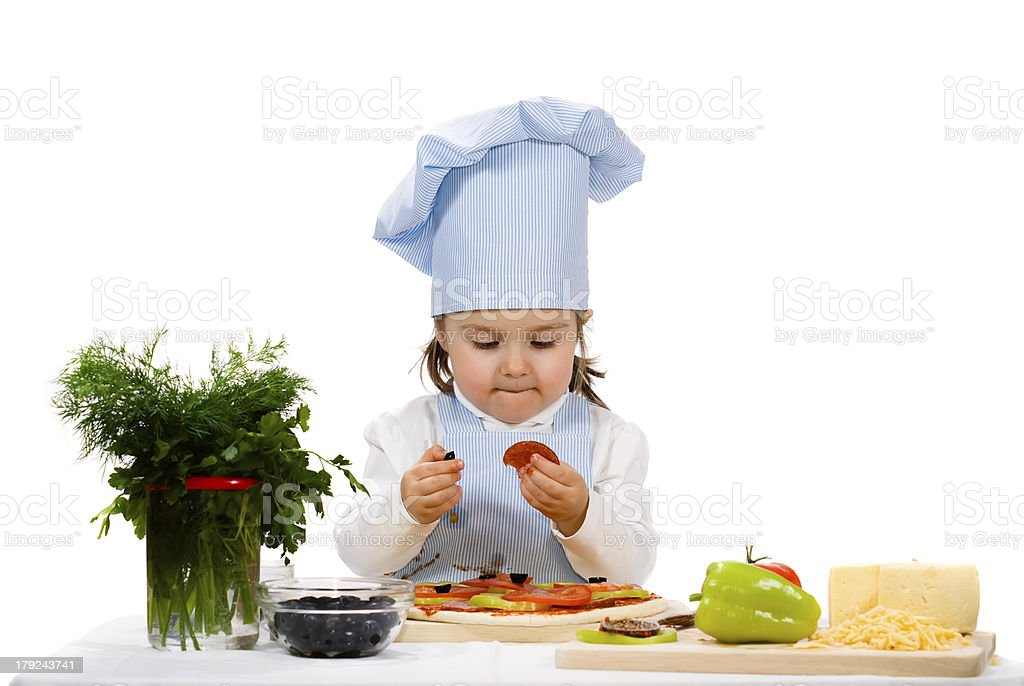 little girl preparing a pizza with salami and vegetables royalty-free stock photo
