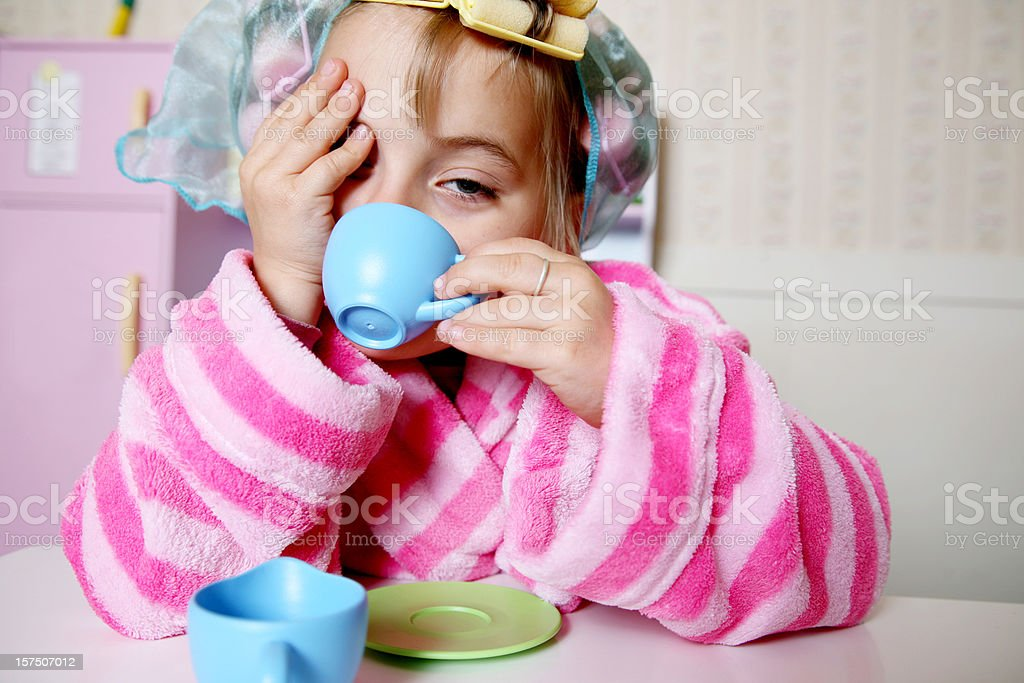 Little girl pretending to be an adult waking up royalty-free stock photo