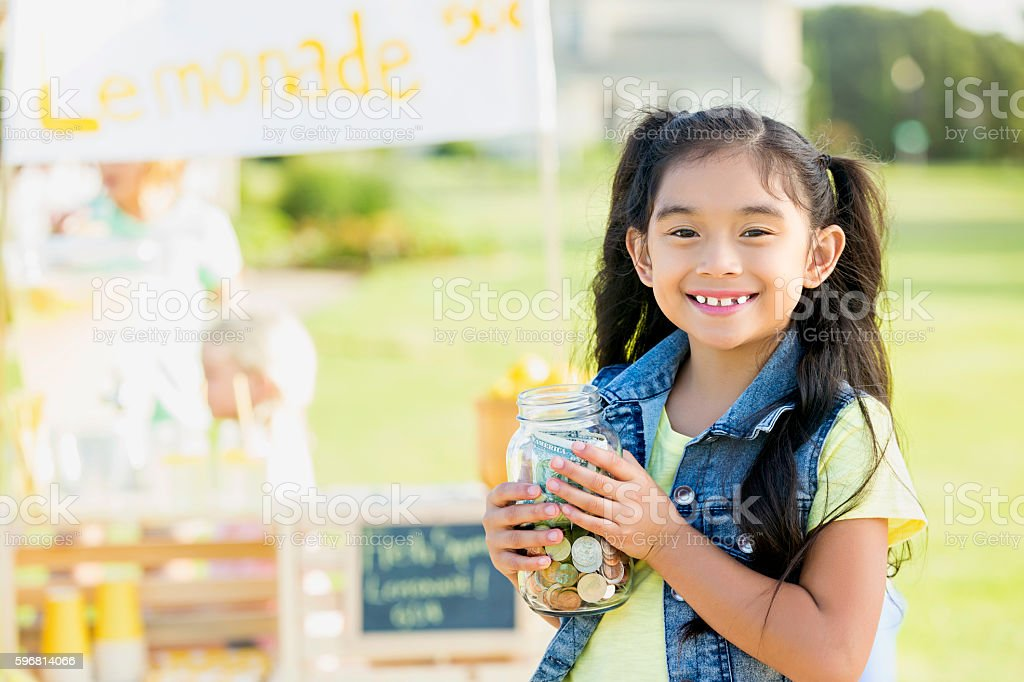 Little girl proudly sells lemonade in her front yard stock photo