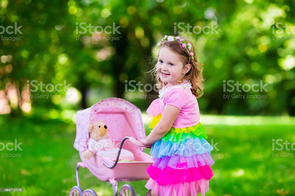 Little girl pushing a toy stoller wth doll stock photo