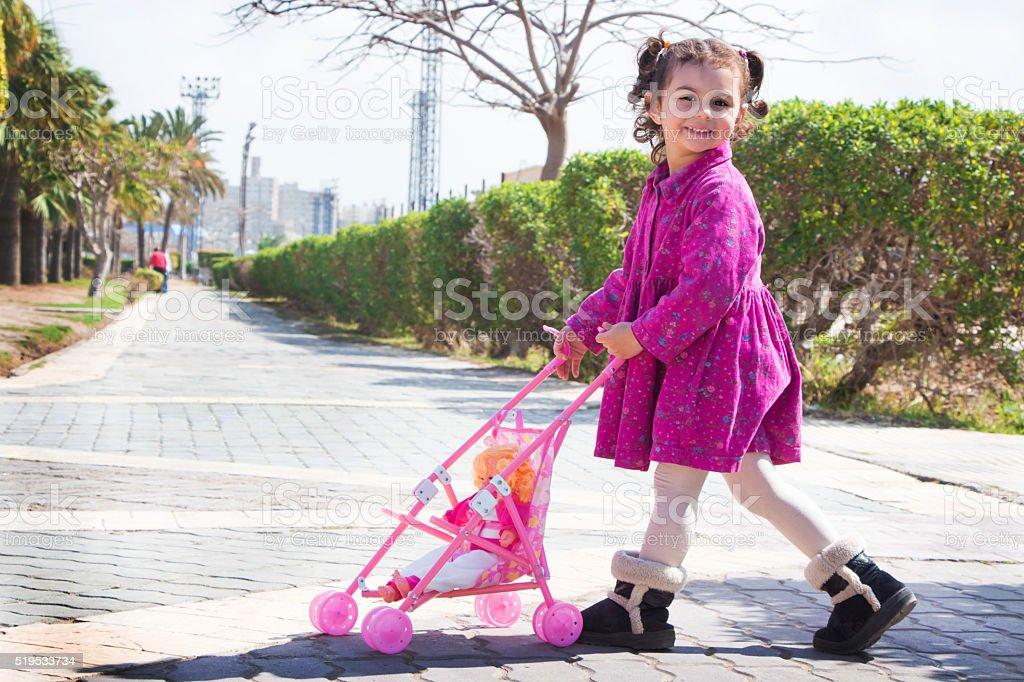 Little girl pushing baby doll in stroller stock photo