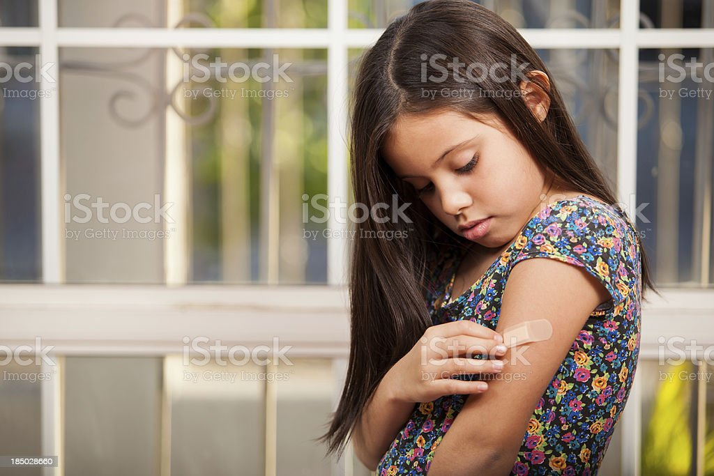 Little girl putting a band-aid on stock photo
