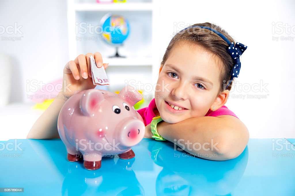 Little girl putting a greenbacks in her piggybank stock photo