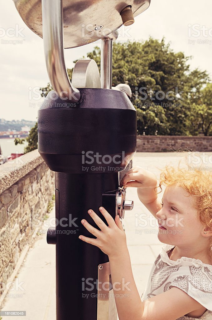 Little girl putting a token in public viewer, Quebec. royalty-free stock photo