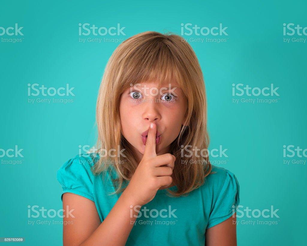 Little girl putting finger up to lips and ask silence. stock photo