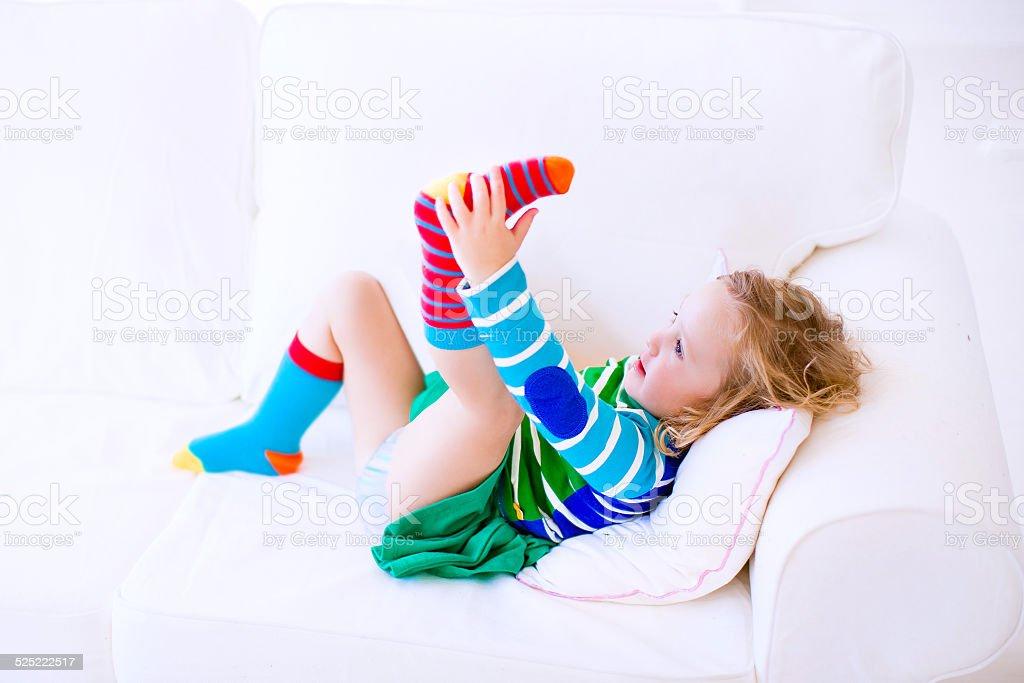 Little girl putting on socks stock photo